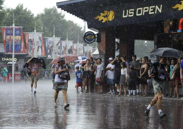 Tennis fans take cover during a downpour at