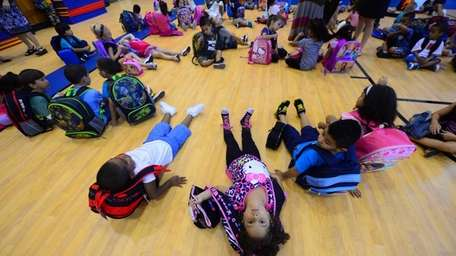 Kindergarteners assemble in the school gym during their