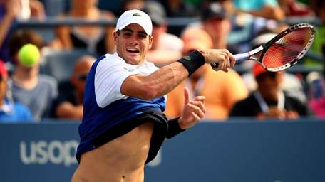 John Isner plays a forehand during his men's