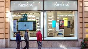 People browse Windows-based Nokia smartphones in Helsinki. Microsoft's