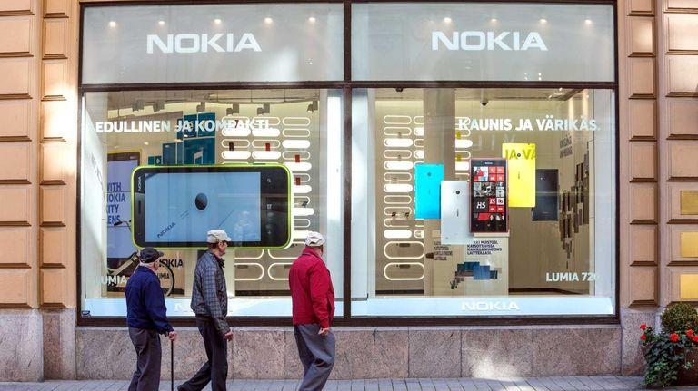 People browse Windows-based Nokia smartphones in Helsinki. Microsoft's