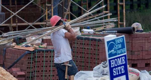 A construction worker carries scaffolding poles for work