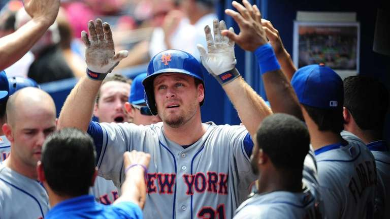 Lucas Duda is congratulated by teammates after hitting