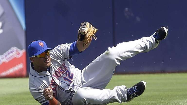 Juan Lagares gets to his feet after making