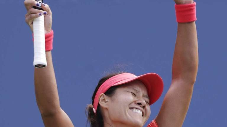 Li Na, of China, reacts after beating Ekaterina