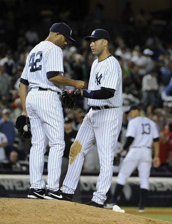 Yankees' Derek Jeter speaks with pitcher Mariano Rivera