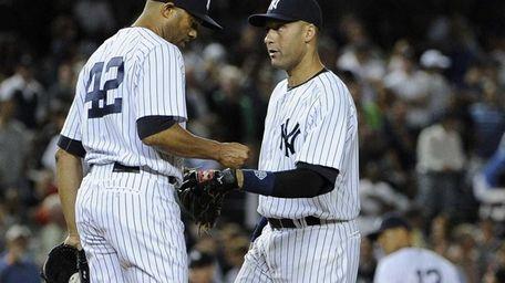 Yankees' Derek Jeter speaks with pitcher Mariano Rivera