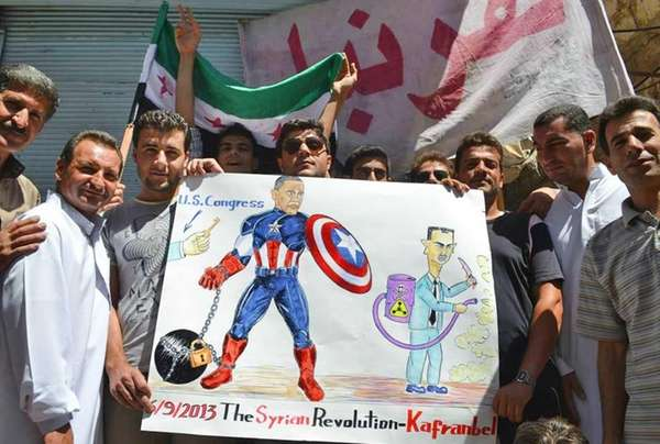 Anti-Syrian regime protesters hold a poster depicting President