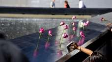 A person photographs roses left behind at the