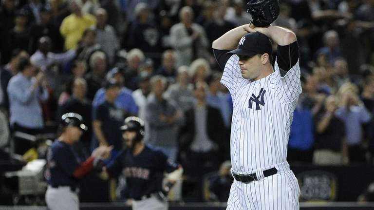 Yankees pitcher Boone Logan reacts after giving up