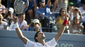 Novak Djokovic raises both his arms in victory