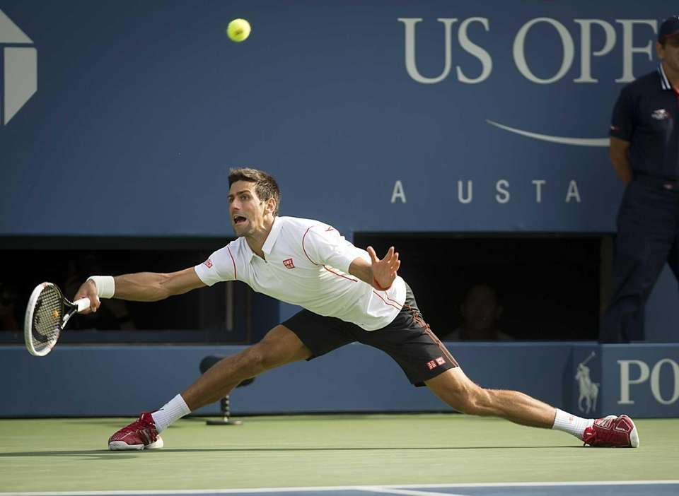 Novak Djokovic stretches while hitting hitting a forehand