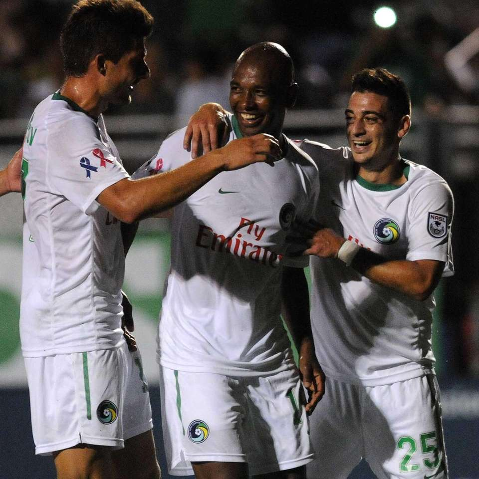 Cosmos midfielder Marcos Senna, center, gets congratulated by