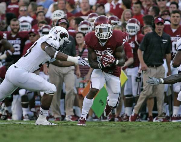Oklahoma running back Brennan Clay evades a Louisiana