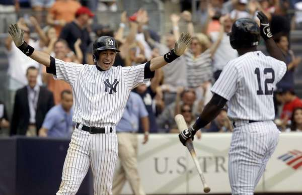 Ichiro Suzuki, left, reacts after scoring on a