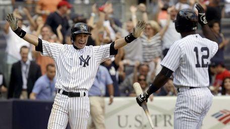 Ichiro Suzuki, left, reacts after scoring on a