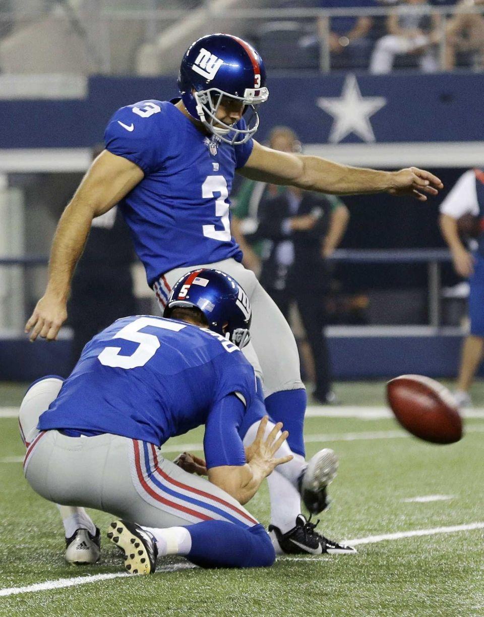 Giants holder Steve Weatherford holds for kicker Josh