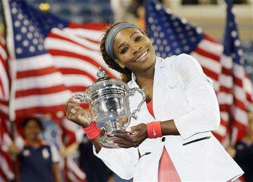 Serena Williams holds up the championship trophy after