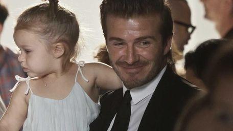 David Beckham carries daughter Harper, 2, as he