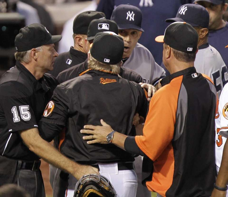 Baltimore Orioles manager Buck Showalter, center, argues with