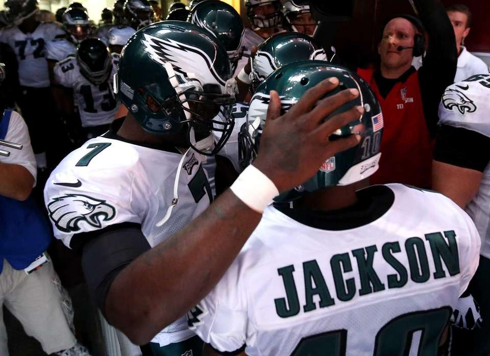 Philadelphia Eagles quarterback Michael Vick huddles with wide