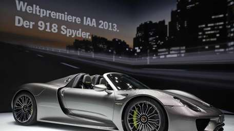 A Porsche 918 Spyder automobile stands on display
