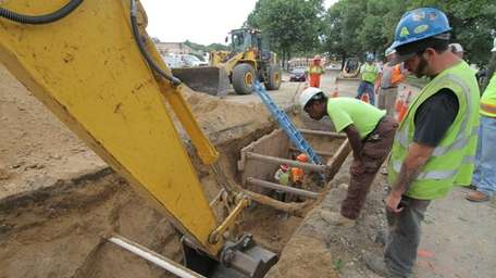 Workers dig at the site of the Sewer
