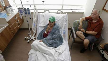 Bev Veals, left, undergoes chemotherapy treatment, accompanied by