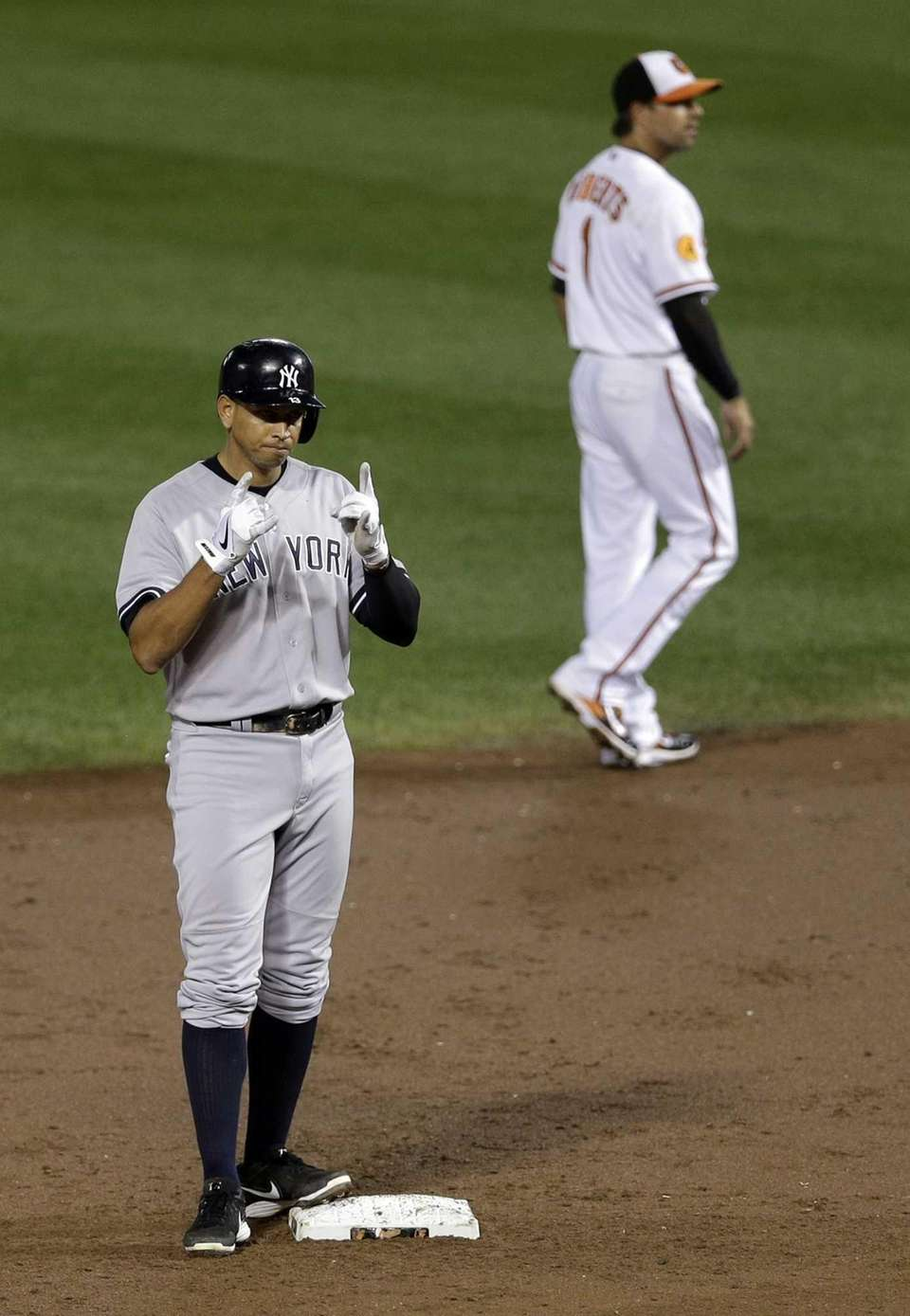 Yankees' Alex Rodriguez, left, gestures after hitting an