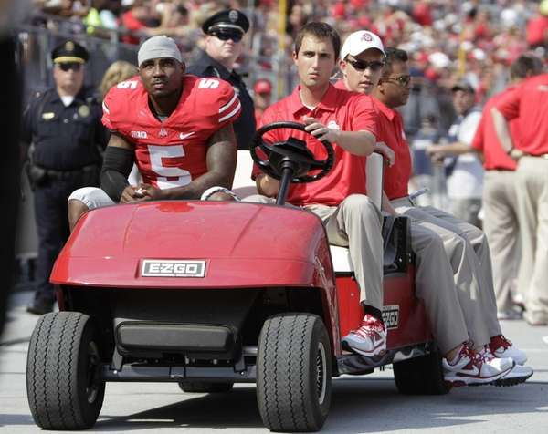 Ohio State quarterback Braxton Miller, left, is carted