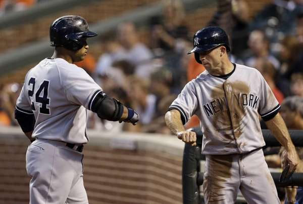 Brett Gardner, right, fist-bumps Robinson Cano after scoring