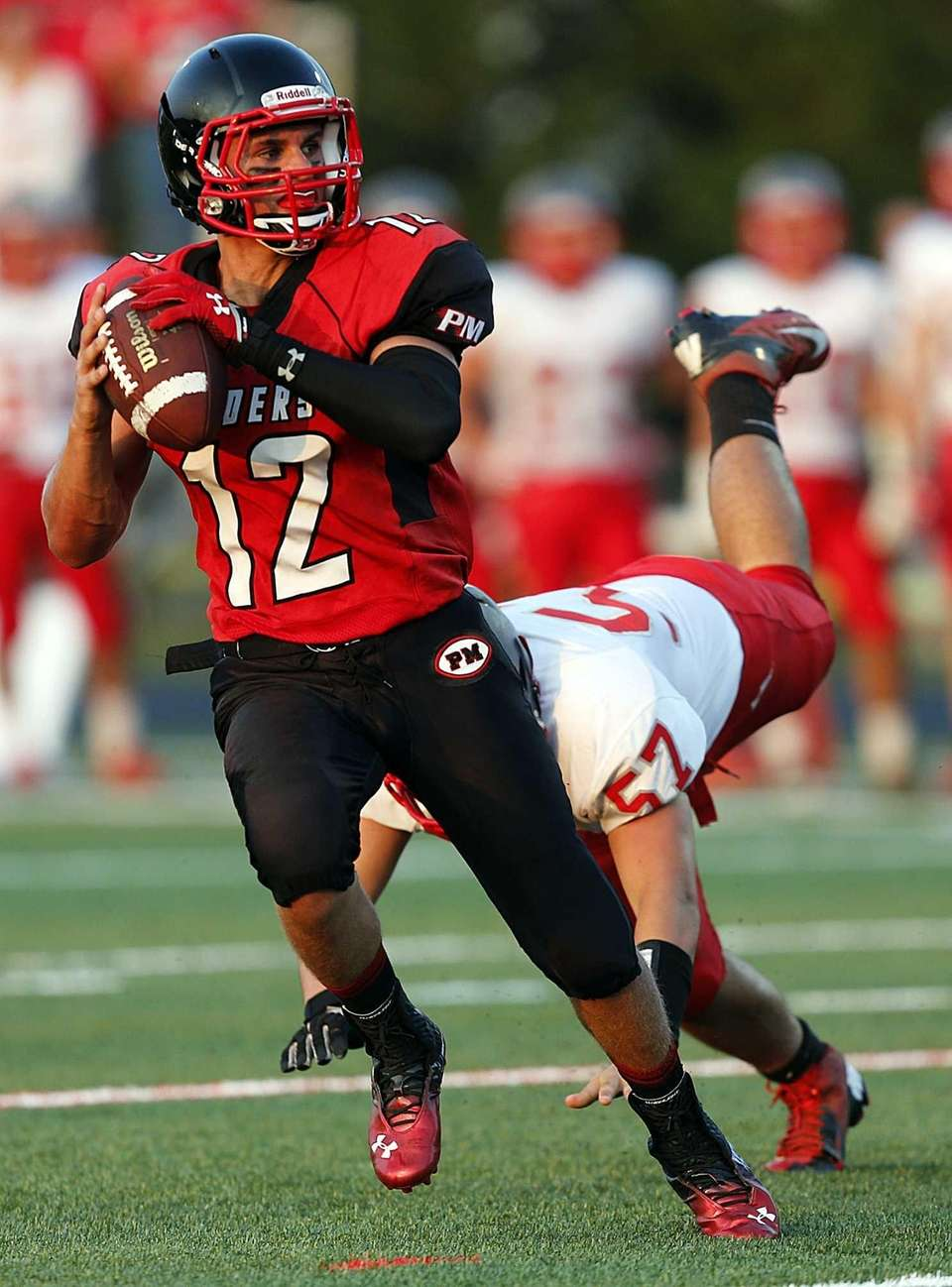 Patchogue-Medford quarterback Anthony Lee steps back to throw
