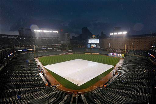 A tarp covers the infield as rain falls