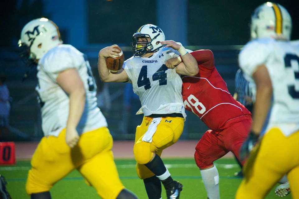 Massapequa running back Paul Dilena is pulled down