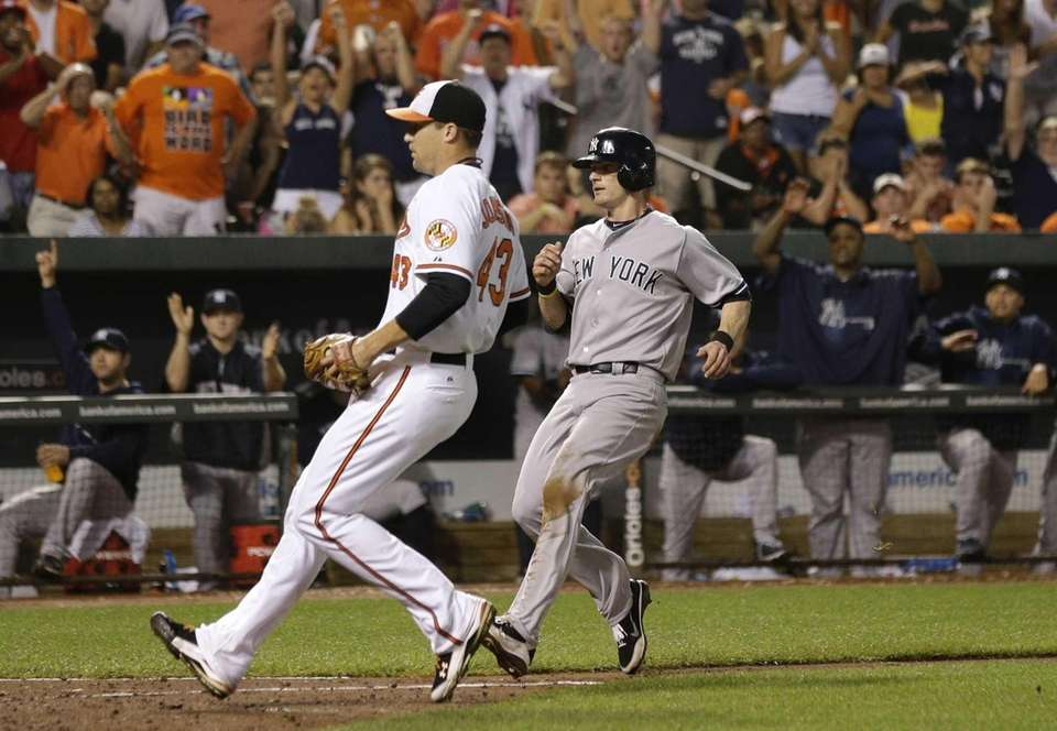 Yankees' Brendan Ryan, right, runs toward home plate