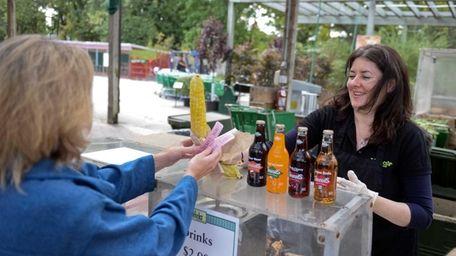 Hicks employee Susan Egan hands over a roasted