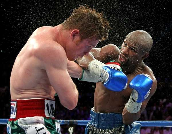 Floyd Mayweather, right, throws a left at Canelo