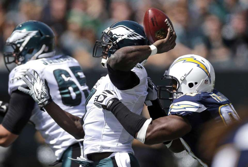Philadelphia Eagles quarterback Michael Vick, left, tries to