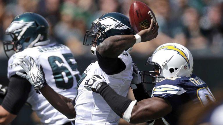 Philadelphia Eagles quarterback Michael Vick, left, tries to