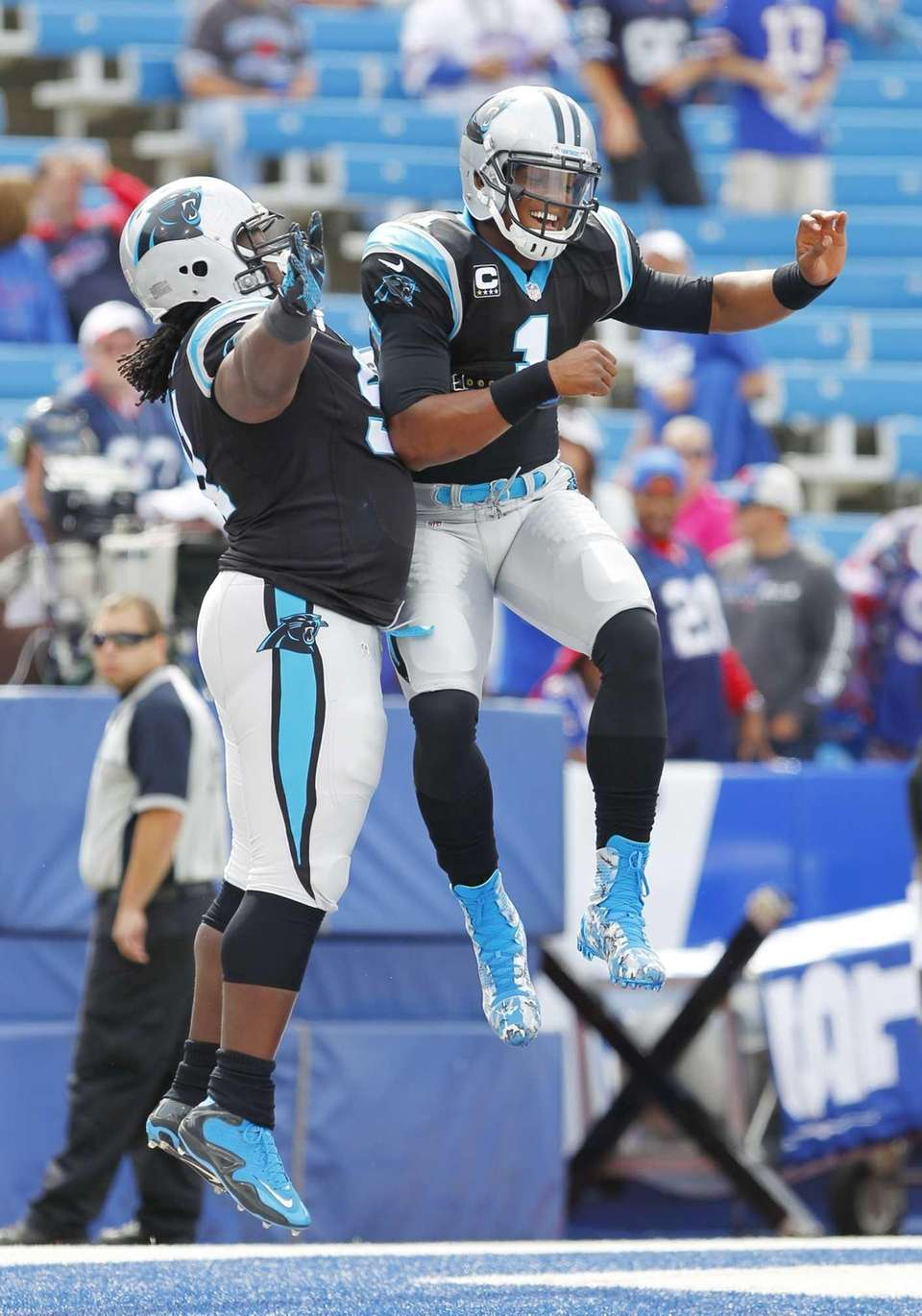 Carolina Panthers quarterback Cam Newton, right, leaps into