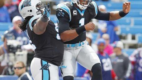 Carolina Panthers quarterback Cam Newton, right, leaps into