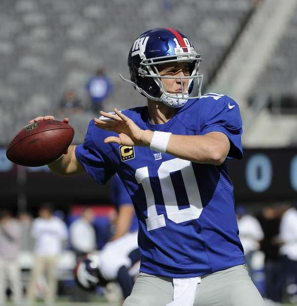 Giants quarterback Eli Manning warms up before action