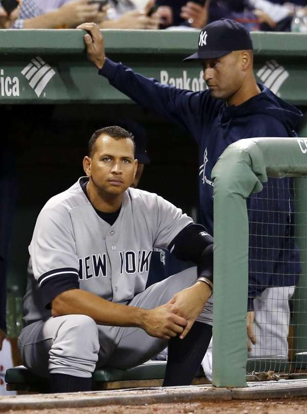 Yankees third baseman Alex Rodriguez, left, sits in