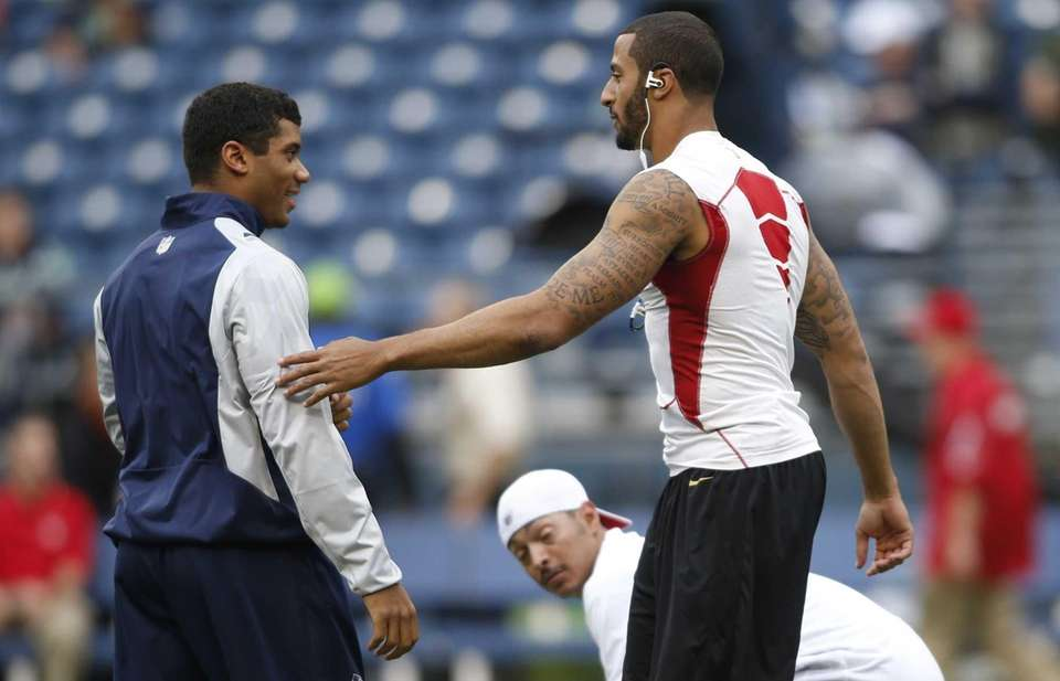 Seattle Seahawks quarterback Russell Wilson, left, greets San