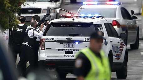 A law enforcement officer aims his rifle to
