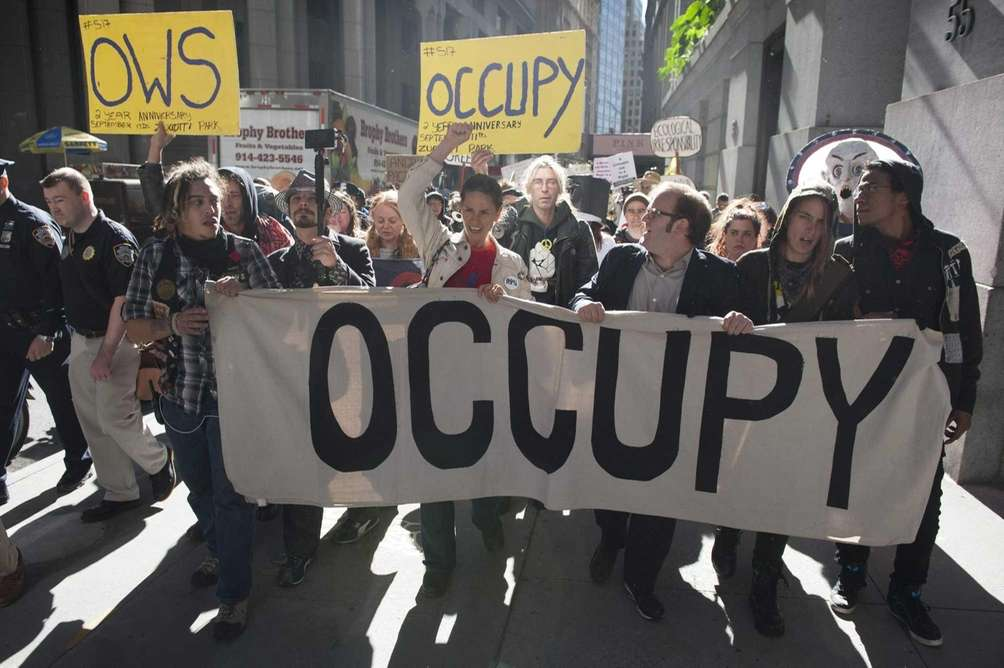 Occupy Wall Street demonstrators march along Wall Street
