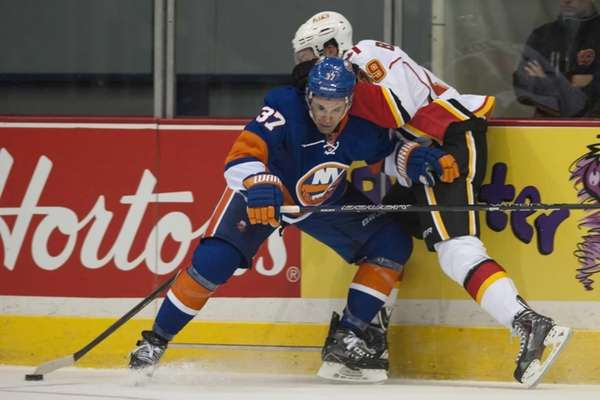 Islanders defenseman Brian Strait, left, holds up Calgary