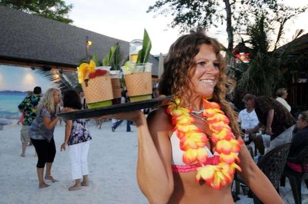 A waitress serves tropical drinks at Off Key