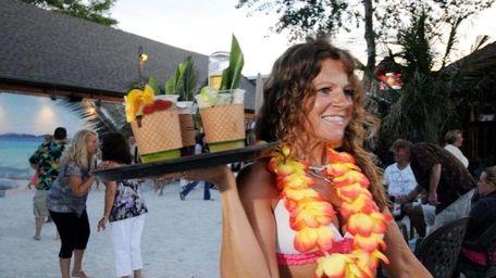 A waitress serves tropical drinks at Off Key