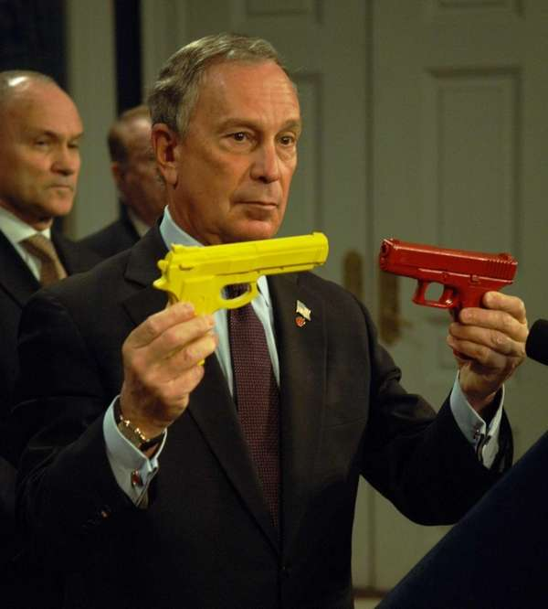 Mayor Michael Bloomberg holds two guns, one a